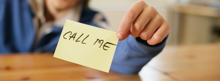 Man holding a note that reads 'call me'